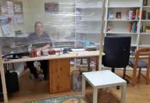 Büchereimitarbeiterin hinter dem neuen Spuckschutz