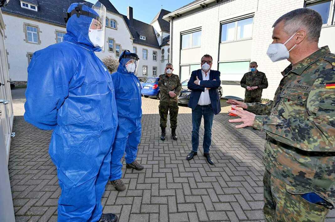 Landrat Dr. Jürgen Pföhler (Mitte) und Generalstabsarzt Dr. Stephan Schmidt (rechts) im Gespräch mit zwei Soldaten, die im Corona-Abstrichzentrum in Grafschaft-Gelsdorf